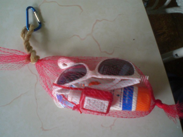 A netted vegetable bag with summer essentials like sunglasses and sunscreen.