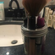 A mason jar with several makeup brushes stored inside.