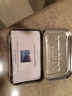 An Altoids mint container holding business cards.