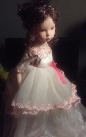 Identifying a Porcelain Doll - doll wearing a white dress with pink trim