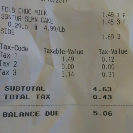 A receipt from a deli for a lunch of salmon patty and green beans.
