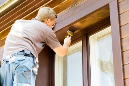 Man Painting Around Brown Windows
