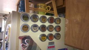 A collection of magnetic spice containers on the side of the fridge.