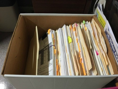 A disorganized box with manila file folders.