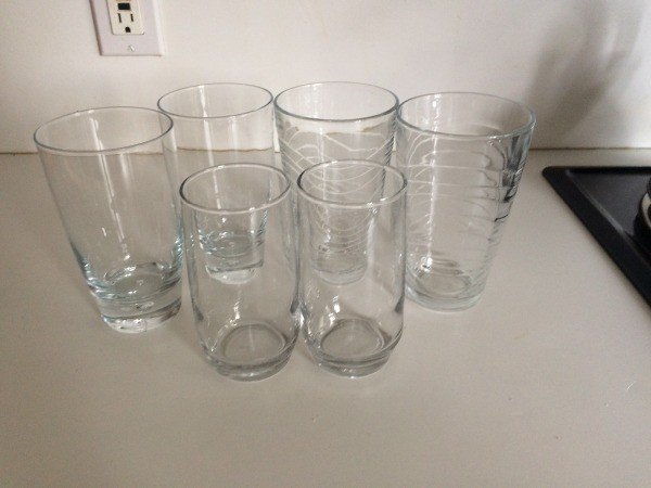 A collection of mismatched glasses on a countertop.