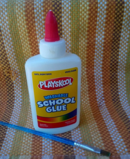 A bottle of white school glue and a paintbrush.