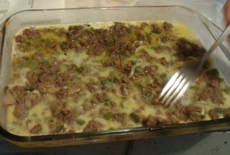 forking Ground Beef Scalloped Potatoes in baking dish