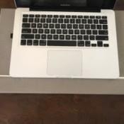 A desk mat under a laptop computer on a wooden desk.
