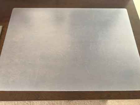 A large desk mat protecting a wooden desk.