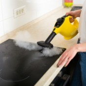 Woman Cleaning stove with Steam Cleaner