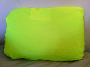 A bright yellow green T-shirt covering a pillow.