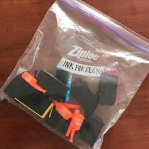 A ziplock bag filled with used printer ink cartridges.