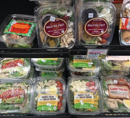 An assortment of different prepackaged salads in a supermarket.