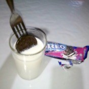 An Oreo cookie placed on a fork, being dipped into a glass of milk.