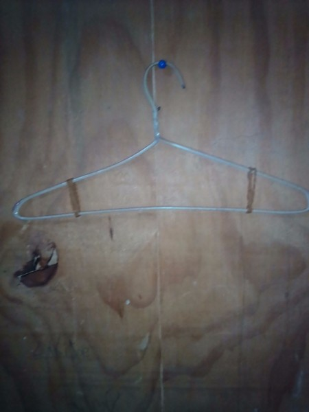 Placing rubber bands on a clothing hanger, to hold clothes.