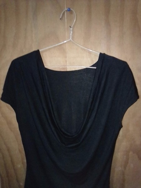 A black top hung on a clothes hangar with rubber bands.