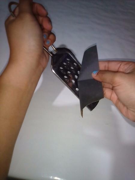 Rubbing sandpaper across a metal food grater.