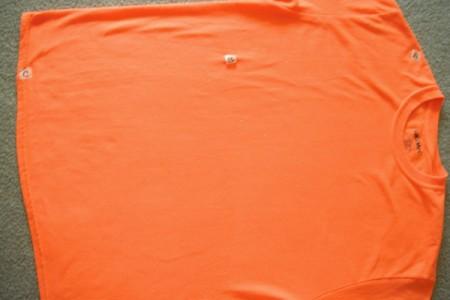 Folding an orange T-shirt.