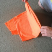 Folding an orange T-shirt.