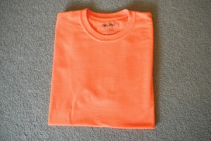 A perfectly folded orange T-shirt.