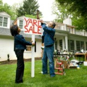 Couple Putting up Yard Sale Sign