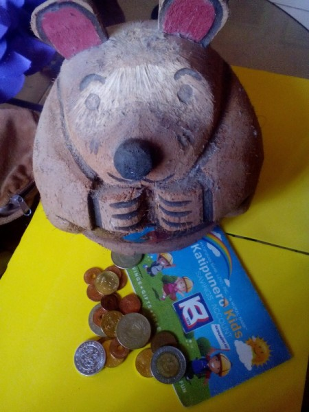 A coin bank with some coins around the base.