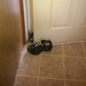 A pair of shoes bracing a door open.