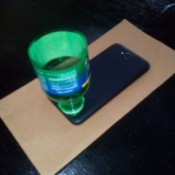 A plastic bottle top placed over the speaker on a phone.