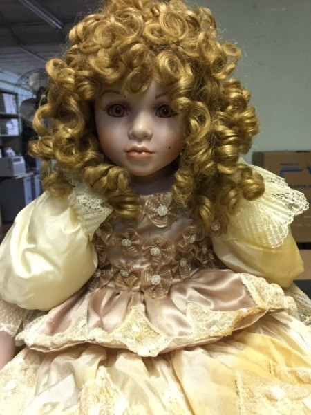 Value of Porcelain Dolls - doll with very curly hair wearing an ecru dress