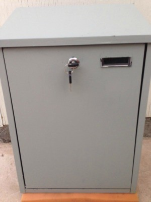 A grey security mailbox with a key.