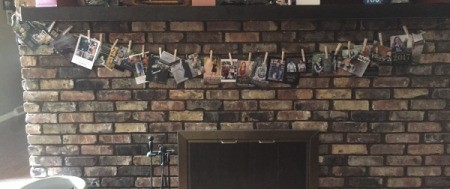 A line of graduation announcement and invites, hanging from a mantle.