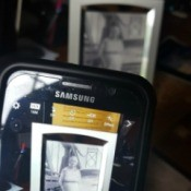 Taking a photo of an old silver picture frame with a smartphone.