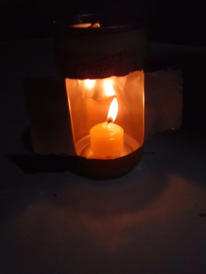 Recycled Can Candle Holder - candle burning inside the can