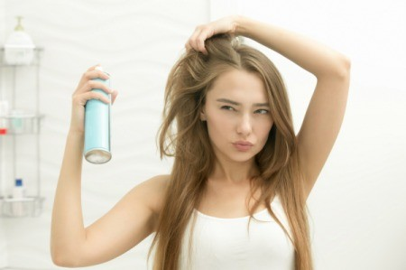 A girl spraying hairspray.