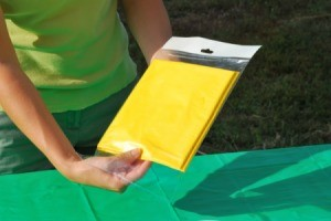 A person holding a yellow plastic tablecloth in their hands.