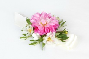 A pink and white wrist corsage.