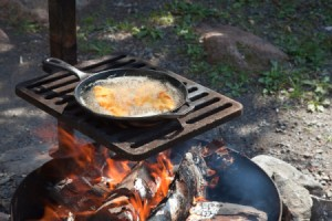 Cooking over a camp fire.