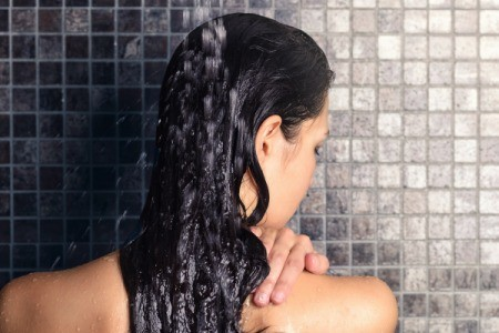 A woman rinsing her hair in the shower.