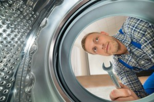 A man repairing a dryer.