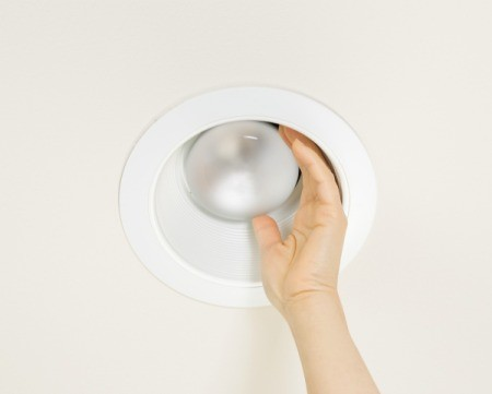A hand trying to remove a bulb from a recessed light fixture.