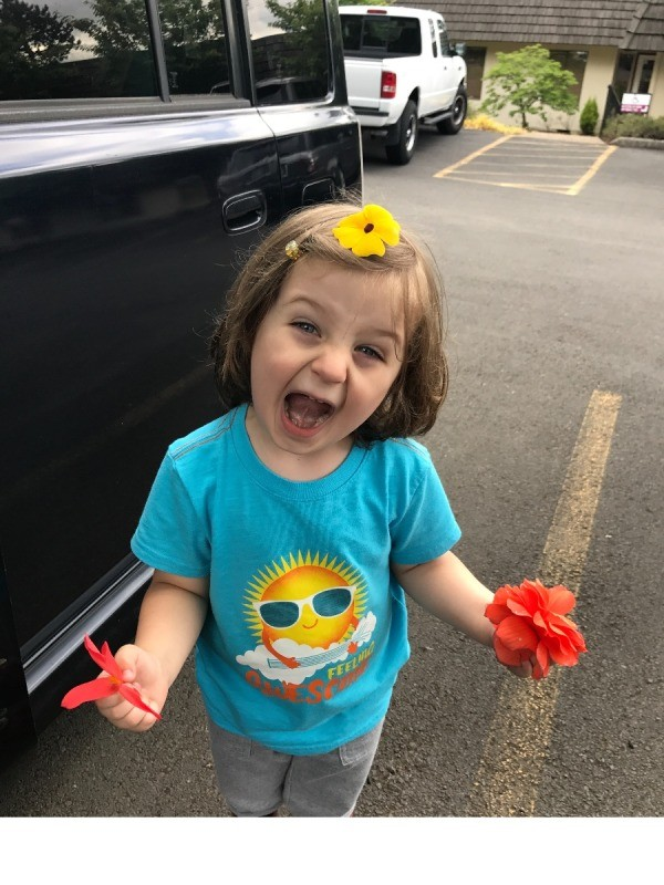 Toddler Fun With Flowers - child holding flowers with one yellow one on the top of his head