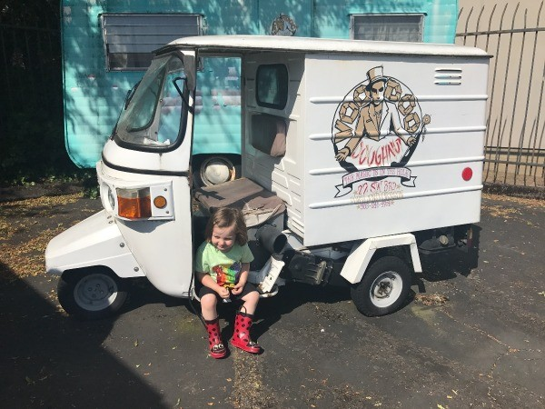 Visting Voodoo Doughnuts (Portland, OR) - young boy sitting on the running board of small three wheel delivery truck