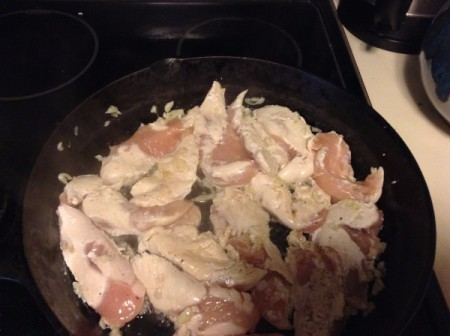 Chicken breast being browned in a large cast iron frying pan.