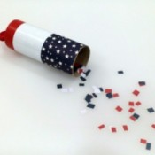 A confetti launcher made from a toilet paper tube, decorated in red, white and blue for the 4th of July.