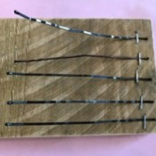 A thumb piano made from bobby pins stapled to a piece of wood.