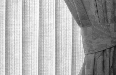 A window treatment of vertical blinds and curtains.