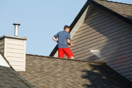 A man standing on a roof cleaning his home's siding with a pressure washer.