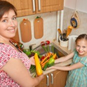 A mom and daughter with vegetables.