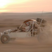 A dune buggy driving fast.