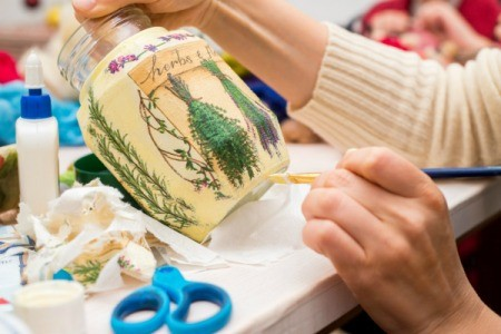Applying craft sealer to a vase.